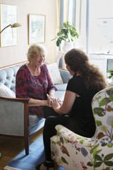 Cheerful grandmother talking to her granddaughter in living room