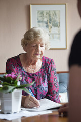 Elderly woman writing something on paper