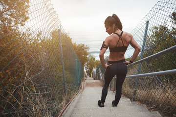 Muscular young woman standing on the stair outdoors