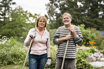 Portrait of smiling active seniors with rake