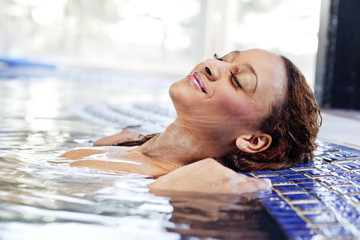 Woman resting her head on pool's edge