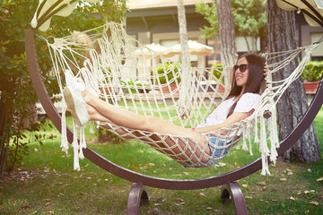 Young smiling woman in sunglasses resting in hammock in backyard
