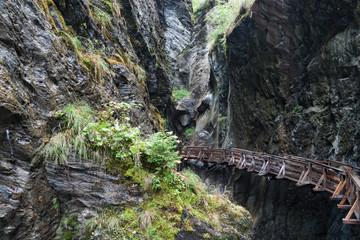 Wooden bridge in mountain canyon.