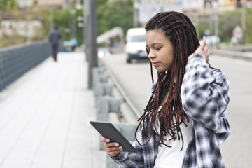 young woman with the tablet on the street