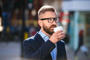 Businessman drinking coffee in the street of London
