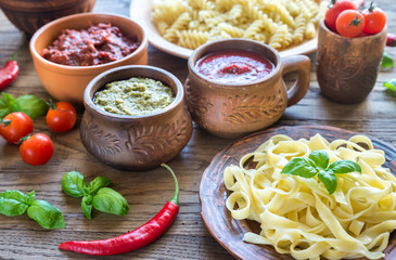Pasta with different kinds of sauce on the wooden background