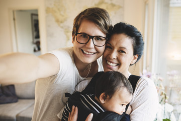 Portrait of smiling lesbian couple with baby girl standing at home