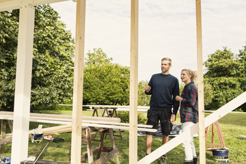 Couple discussing while looking at incomplete shed in farm