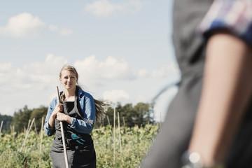 Female farmer with coworker on farm against sky