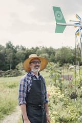 Portrait of happy farmer standing in farm against sky