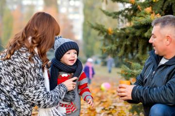 family drinks tea in autumn