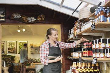 Female sales clerk with tablet arranging bottles on shelf at store