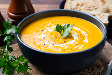 Pumpkin and carrot soup with cream and parsley on dark wooden background