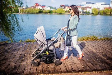happy, beautiful mother walking toddler in urban park with new baby stroller