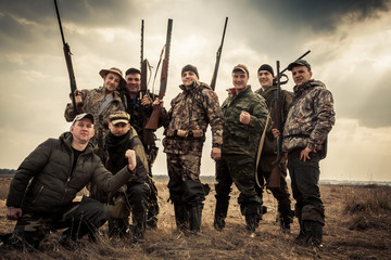 Poster Jacht Hunters standing together against sunrise sky in rural field during hunting season. Concept for teamwork.