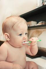 Child brushing her teeth sitting in the bath sink