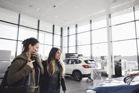Friends looking and choosing car in showroom