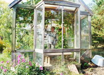 Elderly woman in greenhouse