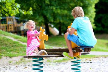 Happy kids enjoying active summer vacation. Adorable toddler girl, having fun outdoors swinging with her brother on playground in the park on a sunny day