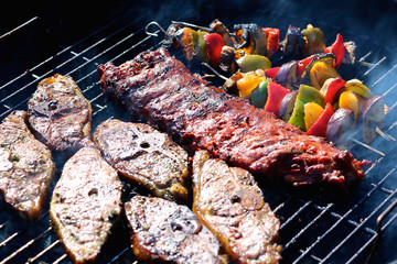 Assorted meat and vegetables on the grill. Lamb steaks, pork ribs, paprika and aubergine roasted on barbecue grid being cooked for summer family dinner.
