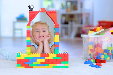 Little preschooler girl building house from plastic blocks. Lovely laughing child, blonde girl of preschool age playing with colorful bricks sitting on carpet in a sunny room at home or kindergarten