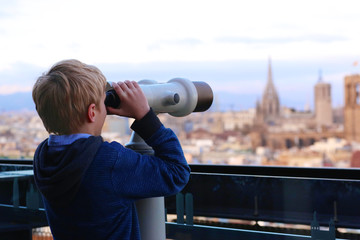 Child enjoying panoramic view of Barcelona, Mediterranean Sea and one of the tallest buildings in the city: Torre Maritima