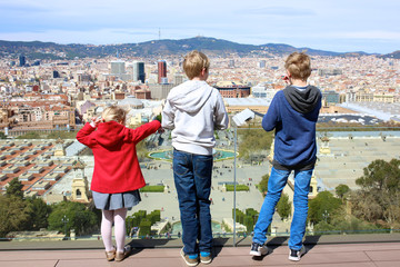 Kids enjoying aerial view on magic fountain and Placa d'Espanya in Barcelona from top terrace of the National Art Museum of Catalonia in Montjuic hill.