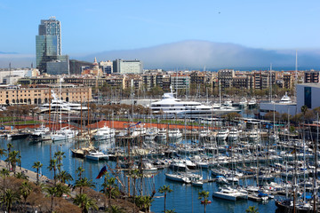 Port Vell and Barceloneta district in Barcelona, Spain. Aerial view from observation platform of Columbus monument. Private luxury yacht boats in the harbour.