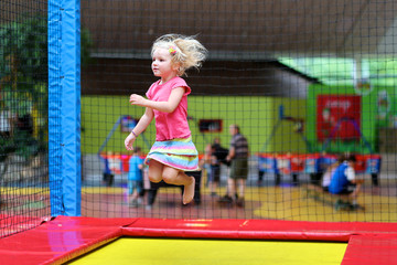 Little child jumping at trampoline in indoors playground. Active toddler girl having fun at sport centre.