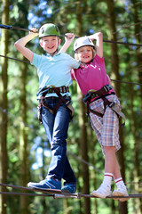 Happy children having fun in adventure park. Two active healthy teenage boys, twin brothers day outdoors climbing on the trees. Friendship and brotherhood concept.