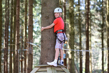 Happy teenage boy climbing on the ropes in adventure park. Healthy child enjoying outdoors teambuilding activity on a summer day.