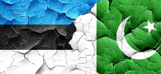 estonia flag with Pakistan flag on a grunge cracked wall