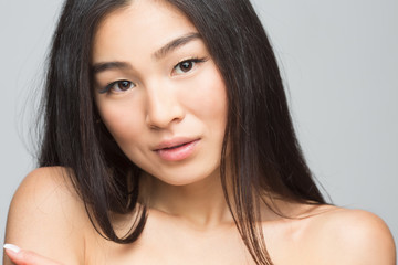 Closeup picture of beautiful woman showing her beautiful shoulders isolated on grey. Happy smiling asian nude lady posing in studio.