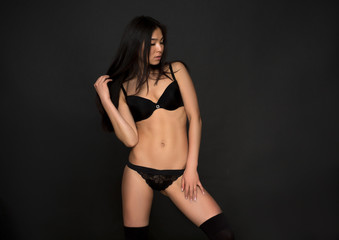 Portrait of beautiful woman with black hair isolated on dark grey background. Attractive fashion asian model in black lingerie or underwear posing in studio.