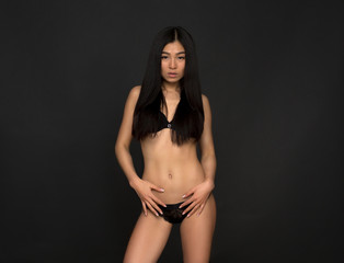 Portrait of beautiful fashion asian model in black lingerie or underwear posing in studio. Pretty woman with black hair looking at camera.