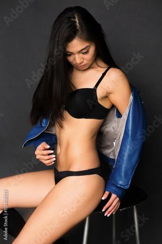 6d81a022f56 Portrait of sexy woman with gorgeous black hair over grey background.  Fashion asian model in black lingerie under blue jacket posing in studio.
