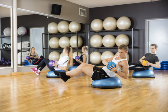 Determined Friends Exercising With Medicine Ball In Gym