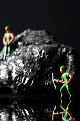 Coal miniature miners / miniature model miners on a piece of coal on a carbon fiber background