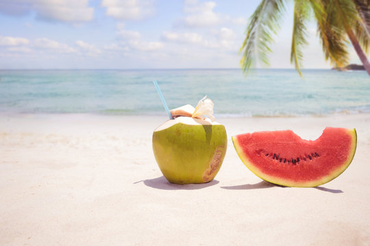 Summer fruit concept with coconut cocktial, watermelon on sandy tropical beach