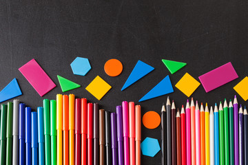"A lot of colorful felt-tip pens and colorful pencils in row and geometric figures on the black school chalkboard as background, concept ""Back to school"""