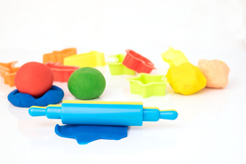 Set of play dough and plastic cutting block on white background
