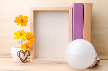 Photo frame with books, flowers and lamp on the wooden table
