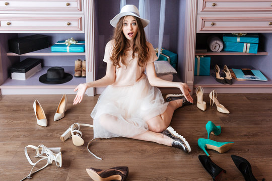 Girl choosing shoes in her wardrobe