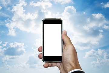 Hand holding mobile phone with blank space on screen, on blue sky with white clouds and bright light behind