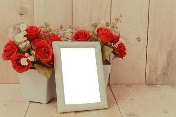 Old wooden picture frame with clipping path and red flowers