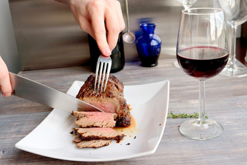 Just cooked roast beef is sliced by young chef on the white plate. Knife, fork, red wine, wine glass, wooden table