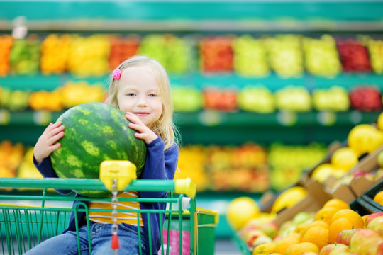 Little girl holding a watermelon in a food store or a supermarket