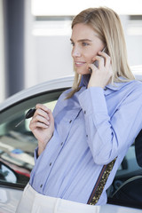 Beautiful blonde women talking on the phone with cars keys in her hands