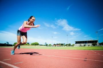 Female athlete running on the running track