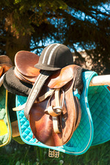 Equestrian sport equipment and accessories hanging on fence